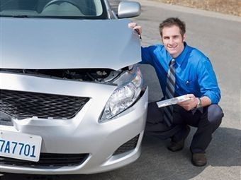 Insurance adjuster in Glendora Califronia inspects a car.
